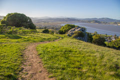 A dirt trail leading downhill on Ring Mountain in Marin County California. An evening sun shines down on a dirt trail on Ring Mountain in Marin County Royalty Free Stock Photo