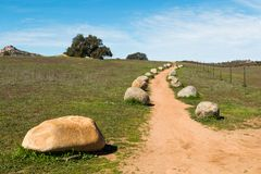 Dirt Trail Lined with Boulders Leading to Hilltop Stock Photo
