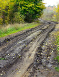 Dirt wet road. Rural landscape in countryside with dirt wet road in the forest. Autumn woods and dirt country road with a auto-tracks after the rain Royalty Free Stock Photos