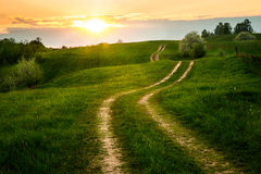 Dirt winding road. The Sun set over the dirt, winding road. May 2016, Masuria, Poland Stock Image