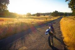 Dirtbike припарковало на заходе солнца на ранчо Калифорнии Стоковая Фотография RF