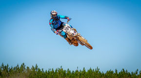 Dirtbike Action Scene. Motorcyclist leaning on a high jump during a dirt bike race Stock Photos