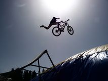 Dirtbike bmx rider jumps against sun Royalty Free Stock Photo