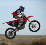 Dirtbike in mid-air. A close-up photo of a dirtbike jumping at a motocross track Stock Photos