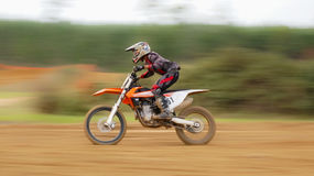 Dirtbike Motion Blur Scene. Motorcyclist leaning foreward and throttling up on a during a dirt bike race Royalty Free Stock Photography