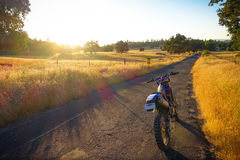 Dirtbike Parked at Sunset on California Ranch. Groveland, California - July 15, 2014: A parked dirtbike on a farm road during a golden late afternoon sunset royalty free stock photography