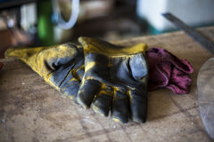 Dirtied welding gloves rest on table. Royalty Free Stock Photo