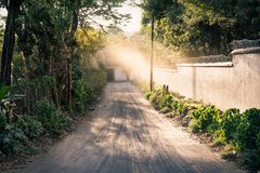 Dirtroad to a coffee plantation finca with sunbeam, Antigua, Guatemala. Dirtroad to a coffee plantation finca lined by trees and wall land with sunbeam, Antigua stock images