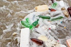 Dirty act. Plastic waste in a stream of dirty water Stock Photography