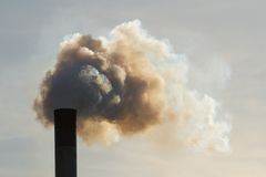 Dirty air. Fumes belch out of the top of an industrial chimney royalty free stock images