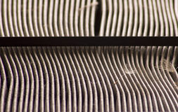 Dirty Air Filter. Close-up of a dirty car air filter; the elements are full of dust and a dandylion seed is in the foreground Royalty Free Stock Image