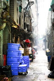 Dirty alley way with cluttered trash and rain royalty free stock image