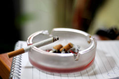 Dirty Ashtray and Cigarette Closeup Isolated. On workplace Stock Photo