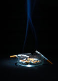 Ashtray And Two Cigarette. Dirty Ashtray And Two Cigarette On the Dark Background Stock Photography