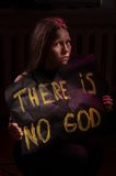 Dirty atheist teen girl holding a banner with the inscription Stock Image
