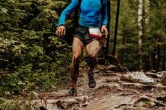 Dirty athlete runner. Running puddles with mud splashing water royalty free stock image