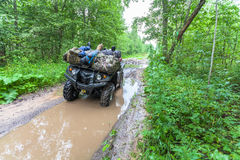Dirty ATV stands with bags and stuff in the deep muddy puddle on the forest road Royalty Free Stock Images