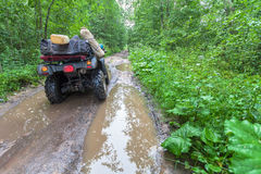 The dirty ATV stands with bags and stuff in the deep muddy puddle on the forest road Stock Image