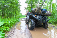 The dirty ATV stands with bags and stuff in the deep muddy puddle on the forest road Royalty Free Stock Image