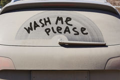 Dirty back window of the car and inscription Wash me please