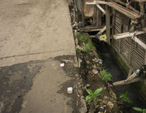 A dirty bamboo bench lay on top of dirty and stinky ditch photo taken in Jakarta indonesia stock image