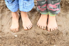 Dirty bare feet. Of two little girls - kids standing on muddy ground Stock Photography