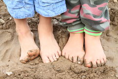 Dirty bare feet. Of two little girls - kids standing on muddy ground Royalty Free Stock Image