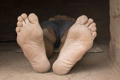 Bare feet of impoverished man resting in hut Royalty Free Stock Images