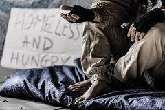 Dirty and barefoot street person. Close-up of dirty and barefoot street person sitting on a blanket and begging Stock Photo
