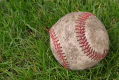 Dirty baseball in grass Royalty Free Stock Photography