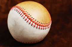 Dirty baseball, white and brown against a dark background Royalty Free Stock Photos