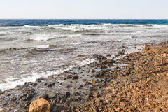 Dirty beach near Aqaba port on Red Sea in winter Royalty Free Stock Image