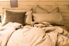 Dirty bed with white pillows and white blanket in the room. Decorate with table lamp. Dirty bed with several design of pillows Royalty Free Stock Photography