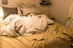 Dirty bed with white pillows and white blanket in the room. Decorate with table lamp. Dirty bed with several design of pillows Royalty Free Stock Image