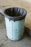 Dirty bin in garage. Black garbage bag in old and dirty plastic bin in garage Stock Images