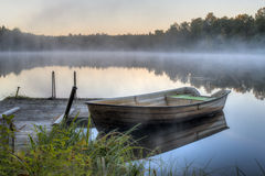 A dirty boat by a wooden pier Royalty Free Stock Photography
