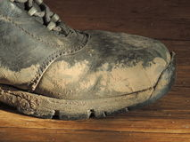 Dirty Boot. Black leather boot stained with bright mud Royalty Free Stock Photos