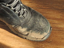 Dirty Boot. Black leather boot stained with bright mud stock image