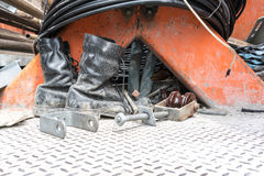 Dirty boot and high voltage electrical replacement parts on non-. Slip floor of electrical maintenance truck Royalty Free Stock Image