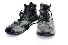 Dirty boots. A pair of dirty black leather boots isolated on a white background Stock Image