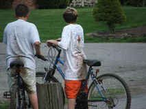 Dirty Boys. Two young boys on bicycles, splattered and dirty from riding through mud puddles royalty free stock image
