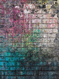 Dirty brick with spots of paint colors Royalty Free Stock Image