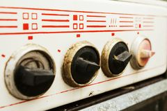 Dirty and broken controllers plate. Kitchen stove white Royalty Free Stock Images