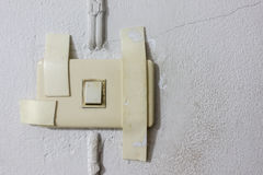 Dirty broken electrical socket on usable light switch Royalty Free Stock Photography