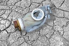 Dirty broken gas mask on cracks Royalty Free Stock Image