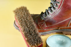 A dirty brown leather boot with polish kit brown leather boot an Stock Photo