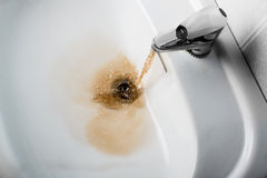 Dirty brown water running into a sink Stock Photo