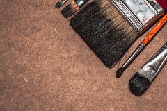 Dirty brushes on a wooden backdrop. Dirty black brushes of different sizes on the wooden backdrop Stock Photography
