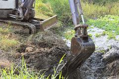 Dirty bucket of backhoe digging  mud and weed in a canal. Royalty Free Stock Image