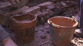 Dirty bucket with clay, soil on the ground for mud house construction royalty free stock photo